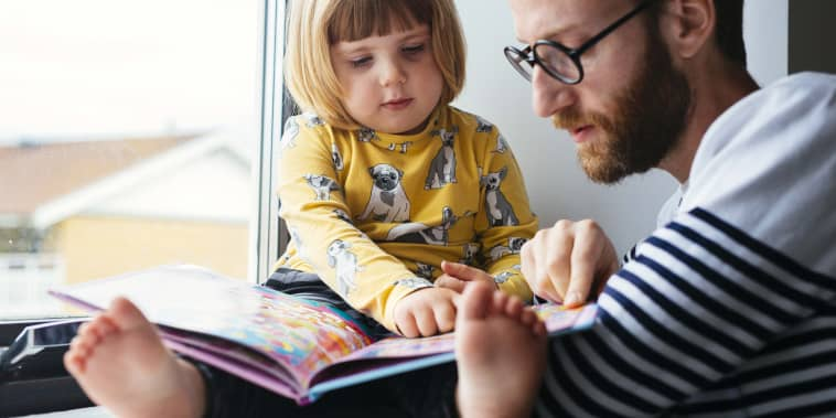 Father and daughter reading book at window