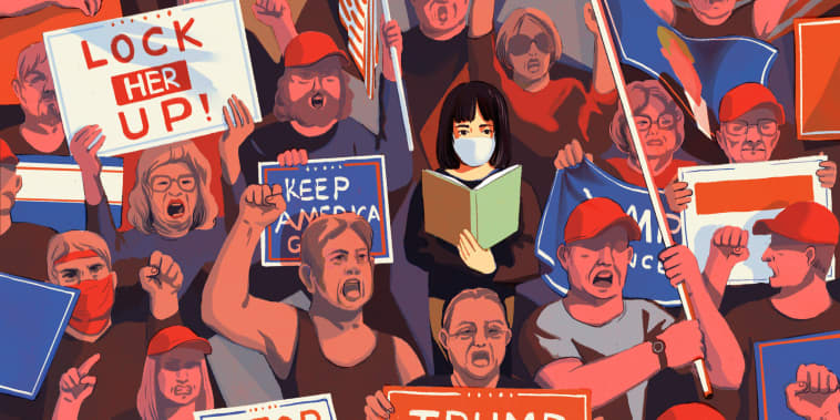 Image: A woman wearing a mask reads a book as she walks through a crowd of Trump supporters.