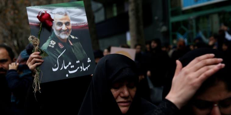 Mourners hold a photo of Gen. Qassem Soleimani in Tehran, Iran,