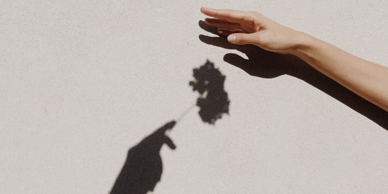 Cropped Hands Of People Against Gray Wall
