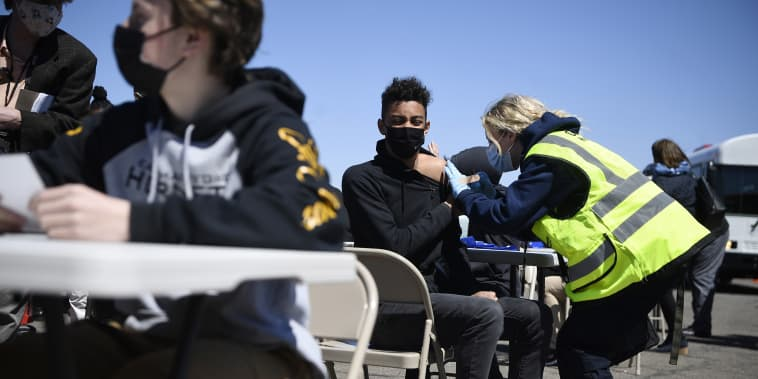 East Hartford High School junior Zander Robinson receives a vaccination from EMT Mary Kate Staunton of Clinton at a mass vaccination site at Pratt and Whitney Runway in East Hartford, Conn., on April 26, 2021.