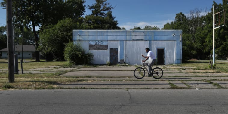 A man rides his bicycle past an abandoned service station in the impoverished east side neighborhood of Saginaw, Mich., on Monday, June 29, 2020.