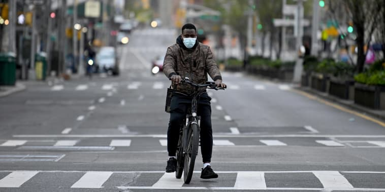 Image: A person wearing a protective mask rides a bike down the middle of an empty street amid the Covid-19 pandemic in New York City.