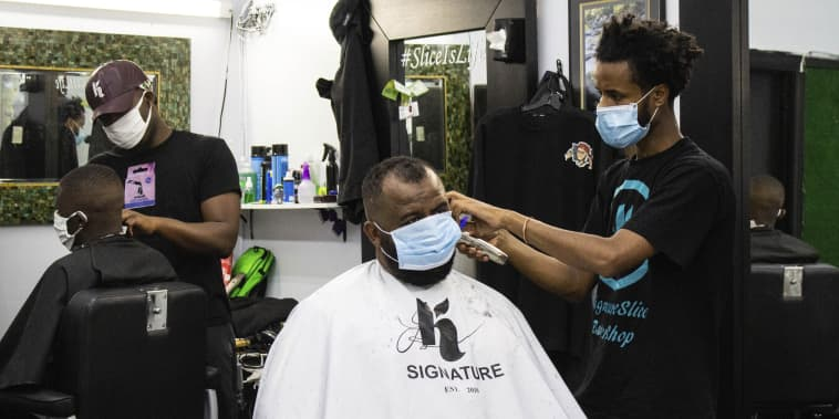 Mohammed Aliyu, left, and Henok Gemeda, right, style customers' hair at K Signature Slice Barber Shop on Lake Street in Minneapolis on July 13, 2020.