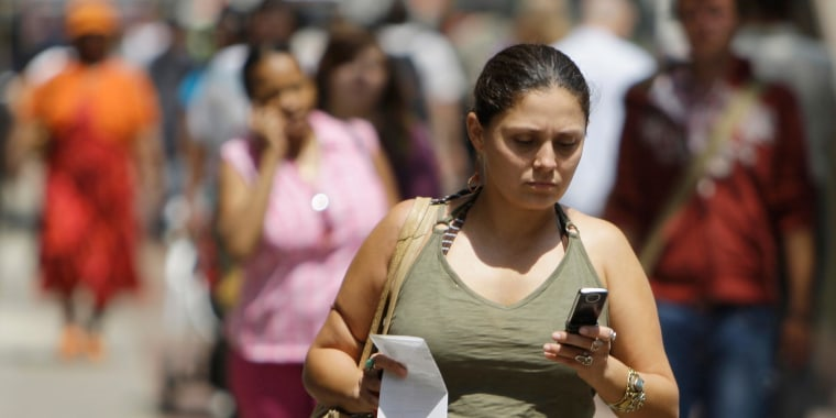 Image: A woman uses her cell phone to text message while walking.