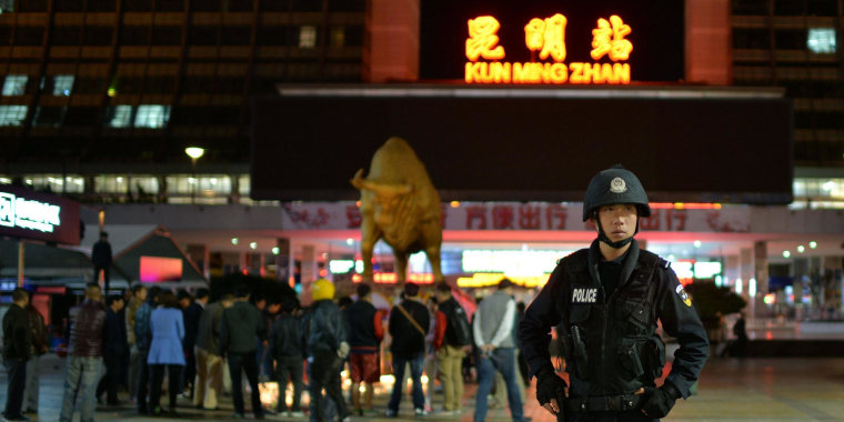 A policeman on guard as mourners light candles at the scene of a terror attack at the main train station in Kunming, southwest China's Yunnan Province, on March 2, 2014. Separatists from China's northwest region of Xinjiang orchestrated the attack on a train station which left 29 dead, the Xinhua news agency reported Sunday, quoting the city government. It said evidence from the scene of the attack late Saturday in Kunming by a group of knife-wielding people pointed to separatists from Xinjiang, a vast region home to the mostly-Muslim Uighur minority.