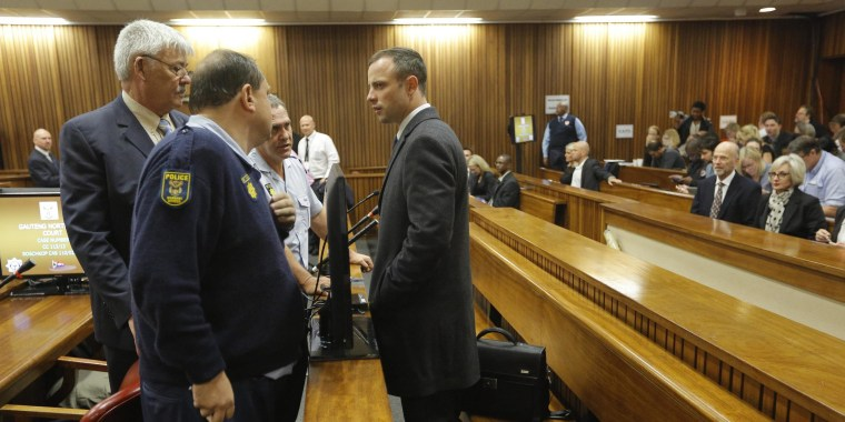 Olympic sprinter Oscar Pistorius talks to his defense team after arriving at the High Court in Pretoria, South Africa, on Tuesday.