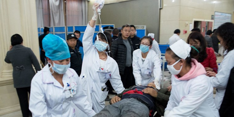 Image: Medical workers moving a man wounded in a deadly stabbing attack at a railway station in China