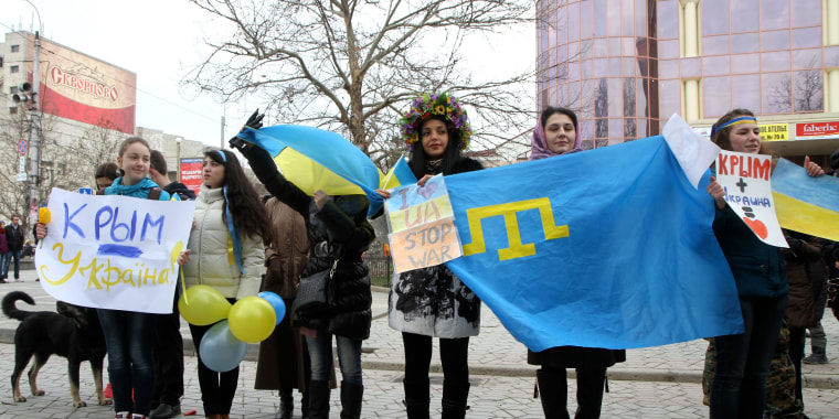"""Protesters in Simferopol today wave Ukrainian and Tatar flags and signs that say """"Crimea is Ukraine."""""""