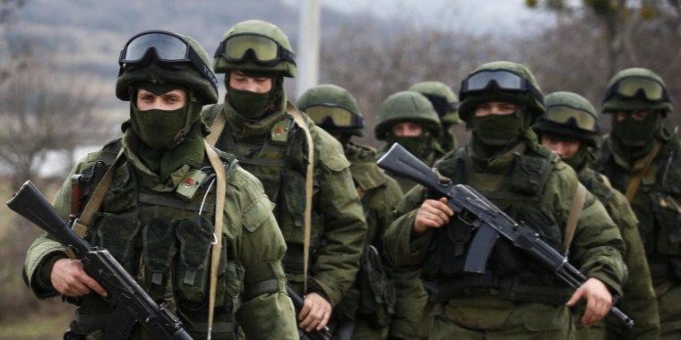 Image: Armed men, believed to be Russian servicemen, march outside an Ukrainian military base in the village of Perevalnoye