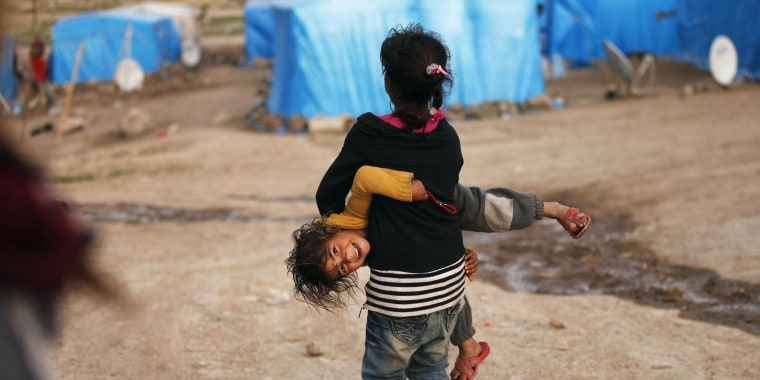 Image: Syrian refugee girls play outside tents in the southeastern city of Kilis near the Syrian-Turkish border