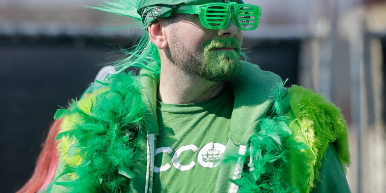 Image: A fan is dressed in green to watch a St. Patrick's Day parade Sunday in Asbury Park, N.J.