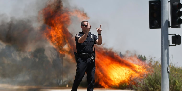 Image: A police officer turns traffic away as flames leap behind him in Carlsbad, Calif.