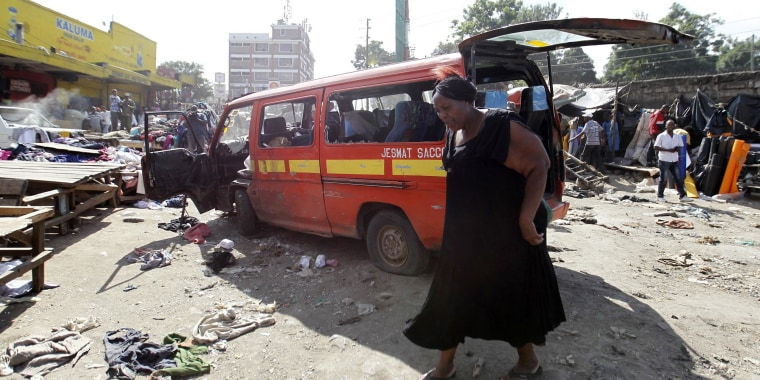 A woman walks near a damaged vehicle at the scene of twin explosions at the Gikomba open-air market for second-hand clothes in Kenya's capital Nairobi on Friday.