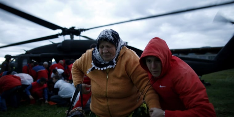 A woman and her son move away from the downwash of an European Union Force (EUFOR) helicopter after being rescued from the flooded Serici village near Zepce, at a heliport in the central Bosnian town of Zenica on Saturday.