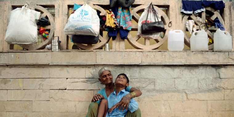 Image: Indian boy Lakhan Kale sits with his grandmother on the pavement in Mumbai