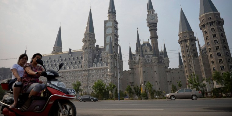 Image: Women ride an electric scooter past buildings, designed based on Gothic architecture, which are part of the Hebei Academy of Fine Arts campus, in Shijiazhuang