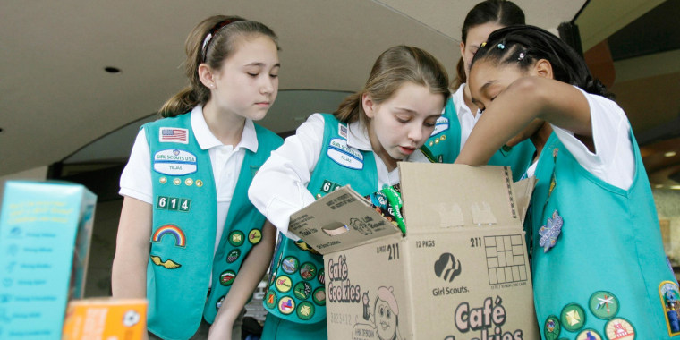 Image: Girl Scouts sort through a case of Girl Scout cookies