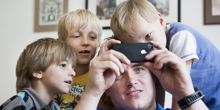 Man with smart phone and young children