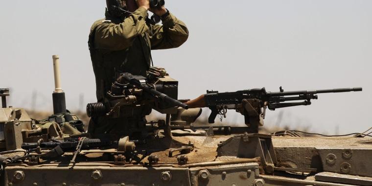 Image: An Israeli soldier uses binoculars on the Israeli-Syrian border in the Golan Heights