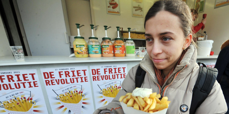 """Image: A woman eats French fries (fried chips) with mayonnaise on the """"Chips Revolution"""" Day"""" in Leuven"""