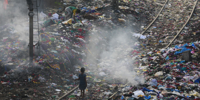 Image: A girl walks on a railway track past piles of dumped garbage in Mumbai, India
