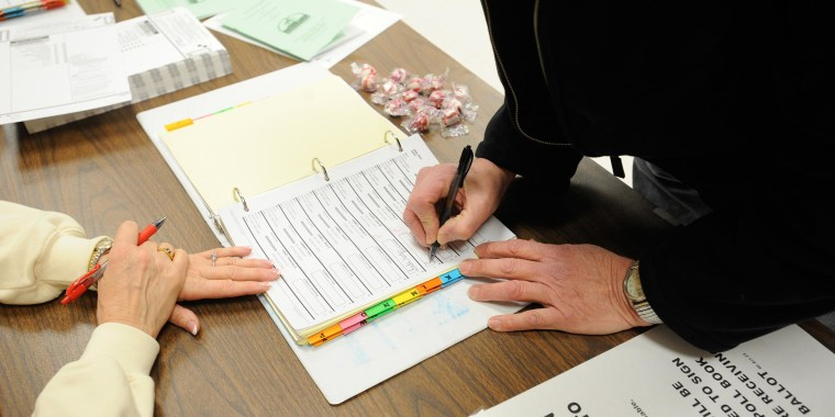 Image: A voter signs the registration log for a school board primary election at the polling place at the Lakeview Community Center in Racine, Wis.