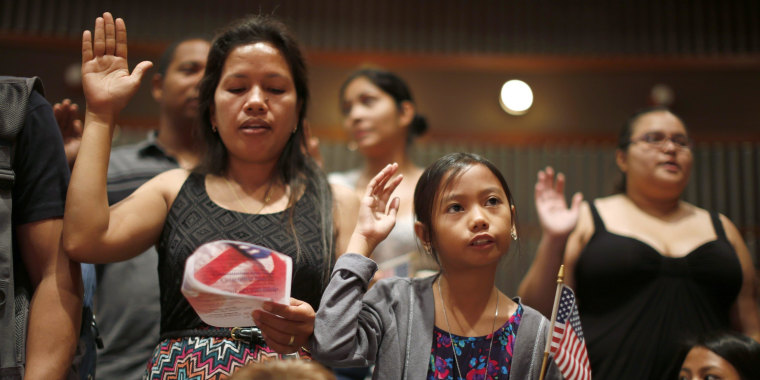 Image: People say the pledge of allegiance at a U.S. citizenship ceremony for 80 immigrant children and youths in Los Angeles