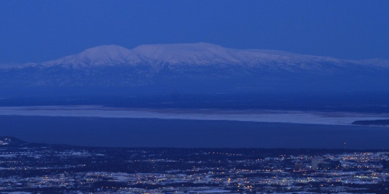 A full moon sets over Mount Susitna, also known as Sleeping Lady, in a view from the Glen Alps Trailhead  on Sunday, Nov. 17, 2013, in Anchorage, Alaska. Temperatures dropped to 13 degrees early Sunday morning. (AP Photo/Dan Joling)
