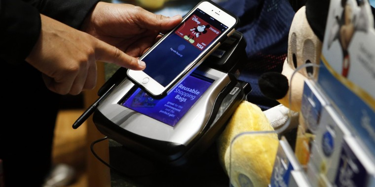 A customer makes a purchase at the Disney Store in Times Square using Apple Pay.