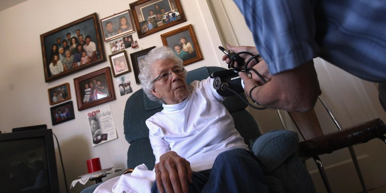 File photo of registered nurse Steve Van Dyke checking the blood pressure of Pauline Zocholl, 94, while on a home health care visit on March 23, 2012 in Westminster, Colorado.