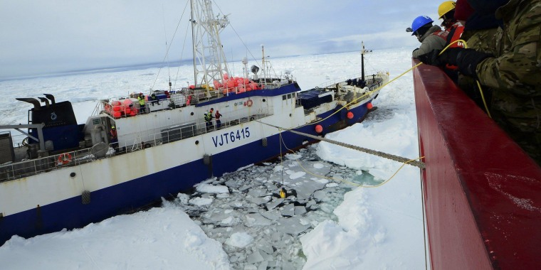 Image: Members of the military dive team aboard Coast Guard cutter, Polar Star, launch a remote operated vehicle into the water to inspect the disabled fishing vessel Antarctic Chieftain, beset by ice near Cape Burks