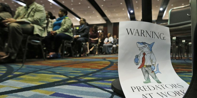 A sign warning of predatory payday lenders leans up against a chair during a speech by Consumer Financial Protection Bureau Director Richard Cordray, in Richmond, Va., Thursday, March 26, 2015.