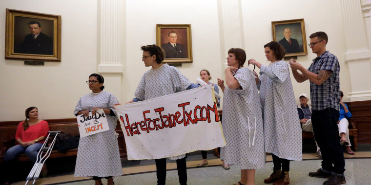 Image: Activists tie on hospital gowns as they prepare to protest House Bill 3994 in the rotunda of the Texas Capitol, Friday, May 22, 2015