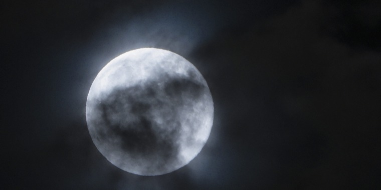 Blue moon seen through the clouds in the sky over Skopje, The Former Yugoslav Republic of Macedonia, 31 July 2015.