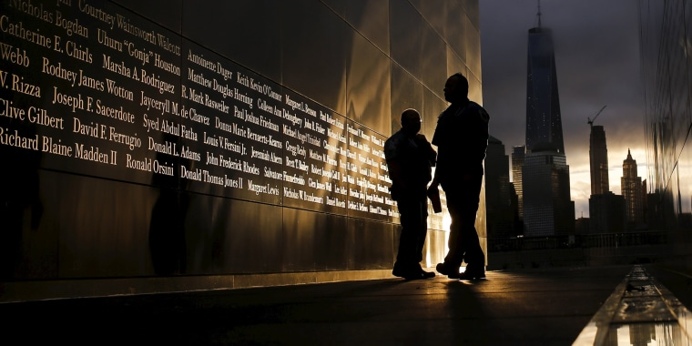 Image: People read the victims' names of the 9/11 Empty Sky memorial