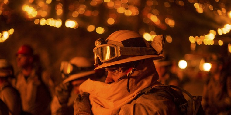 Image: Firefighter covers his face while battling the Butte fire near San Andreas
