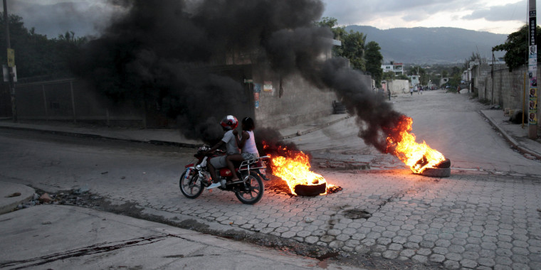 Image: A motorbike passes burning tyres at a barricade during protests after the announcement of the results of the presidential election, on a street in Port-au-Prince, Haiti