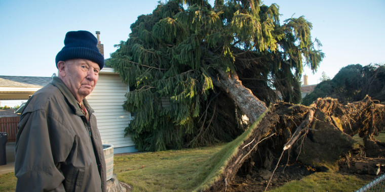 Image: ay Bly checks out the damage to his home in Spokane, Wash.