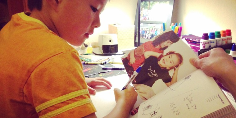 "Sharon H. Chang's son with a copy of Kip Fulbeck's ""Mixed: Portraits of Multiracial Kids."""
