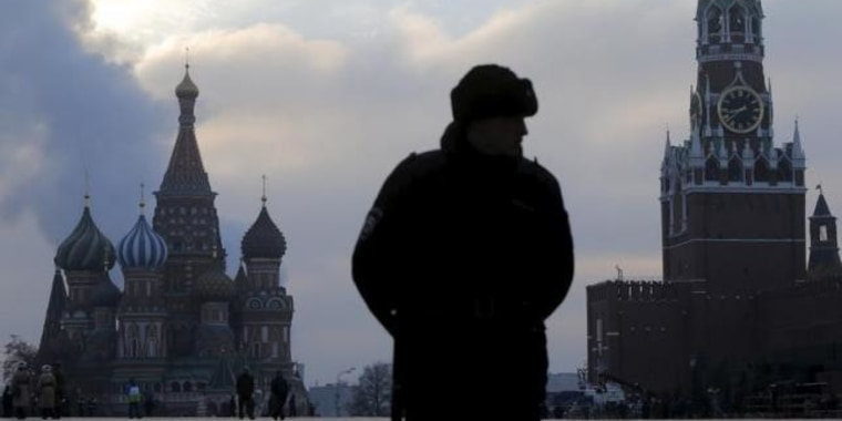 An Interior Ministry member stands guard on Red Square with St. Basil's Cathedral and the Spasskaya Tower of the Kremlin seen in the background in central Moscow