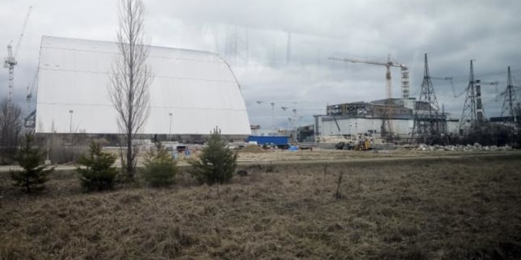 A general view shows a containment shelter for the damaged fourth reactor and the New Safe Confinement structure at the Chernobyl Nuclear Power Plant