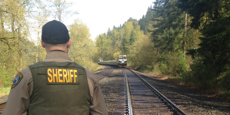 A deputy looks at evidence after two people were struck by a train in Oregon.