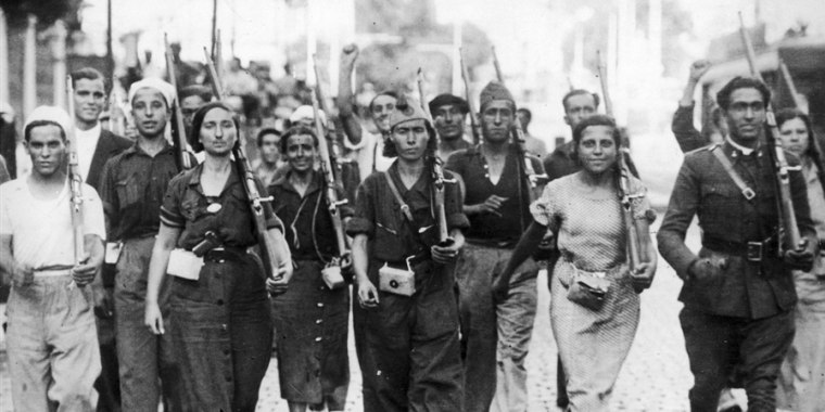 Male and female militia fighters march at the beginning of the Spanish Civil War in July of 1936.