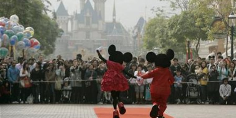 People dressed as cartoon characters Mickey and Minnie greet visitors with their latest Year of the Mouse costumes at Hong Kong Disneyland