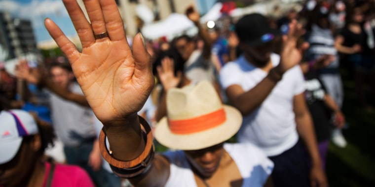 People pray during a rally at City Hall in Baltimore, where hundreds of jubilant people prayed and chanted for justice days after the city's top prosecutor charged six officers involved in Freddie Gray's arrest on May 3, 2015.
