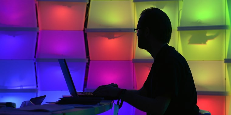 Man at computer surrounded by colorful squares