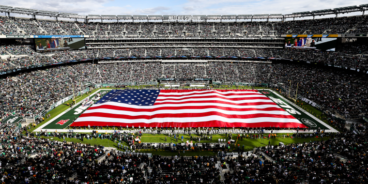 Image: A giant American flag is unfurled on the field in honor of military veterans