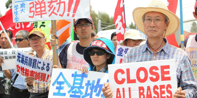 Image: Protesters hold signs outside Kadena Air Base on May 20.