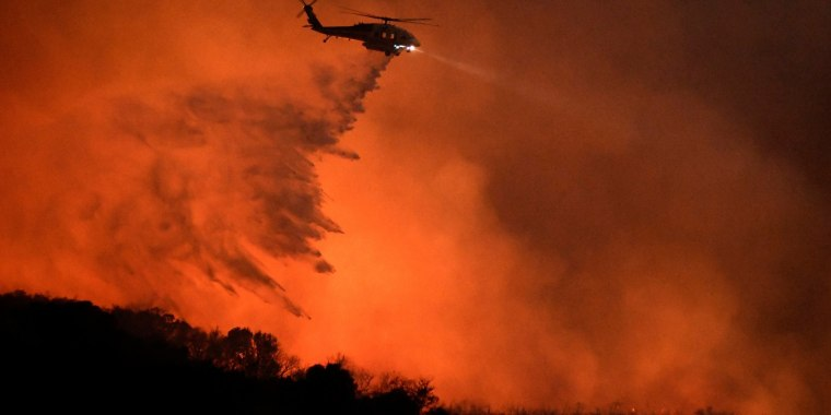 "Image: A helicopter makes a water drop at the ""Old Fire"", which burned in Calabasas, California"